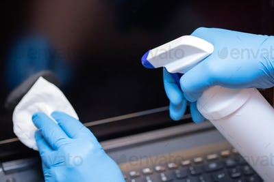 Hands cleaning laptop computer to avoid coronavirus infection