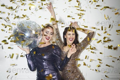 Happy woman with disco ball dancing under shower of confetti