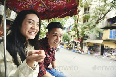 Couple traveling by Vietnamese  rickshaw and pointing on something