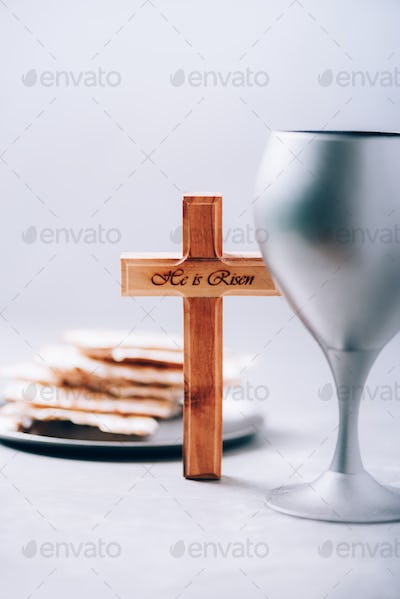 Matzos unleavened bread, chalice of wine, wooden cross on grey background. Christian communion for