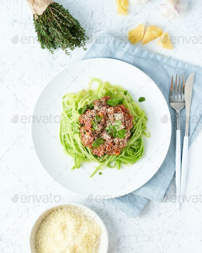 Keto pasta Bolognese with mincemeat and zucchini noodles. Top view, close up, vertical.