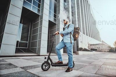 Elegant man with electro scooter is smoking vape