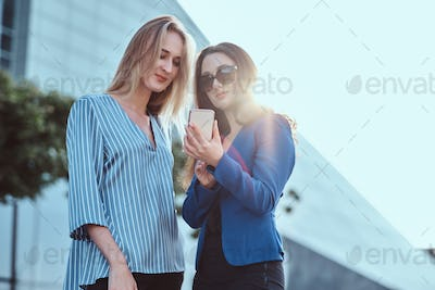 Two women are watching something on smartphone