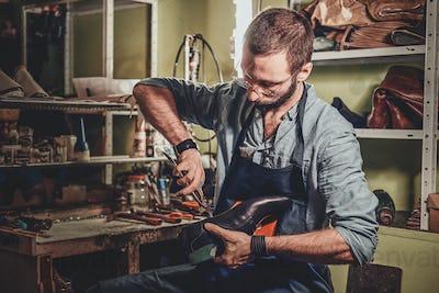 Cobbler is working on shoe sole