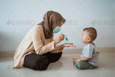 muslim woman applying hand sanitizer to her son