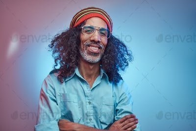 African Rastafarian male smiles and looks at the camera standing with his arms crossed.