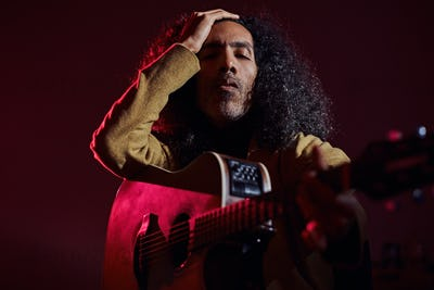 Man is playing guitar while posing for photographer