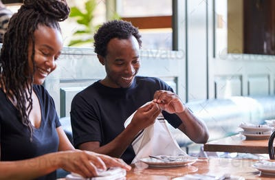 Male And Female Waiters Folding Napkins In Restaurant Before Service