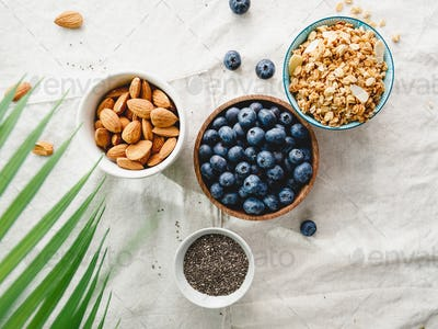 Top view of breakfast ingredients like cereal, almond, blueberry and chia seeds