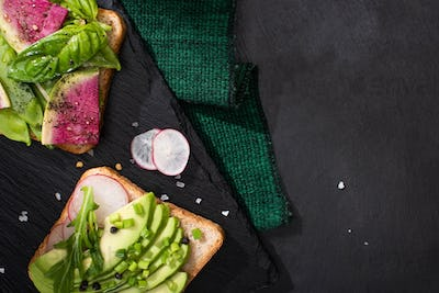 top view of vegetarian healthy sandwiches with radish and avocado on cloth and stone board