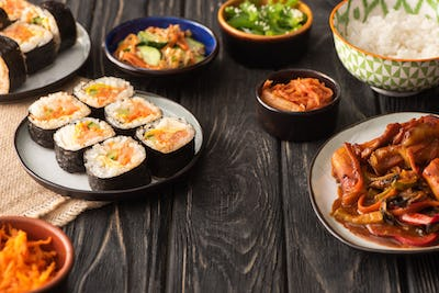 selective focus of traditional gimbap near tasty korean dishes on wooden surface