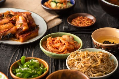 selective focus of spicy kimchi near topokki and korean side dishes