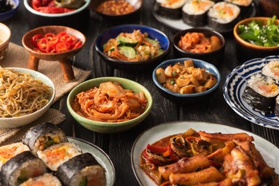 selective focus of traditional kimchi and topokki near tasty korean dishes on wooden surface