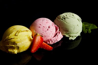 delicious lemon, strawberry and mint ice cream balls isolated on black