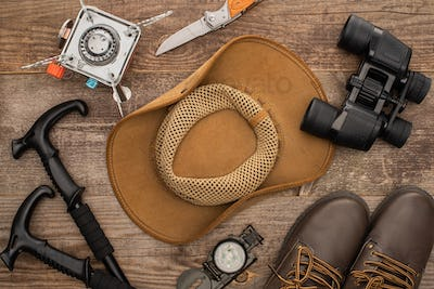 top view of hat, boots, hiking poles, binoculars, jackknife and gas-burner on wooden surface