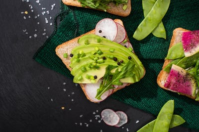 top view of fresh toasts with radish and avocado on green cloth