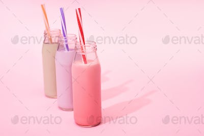 Bottles of colorful berry, strawberry and chocolate milkshakes
