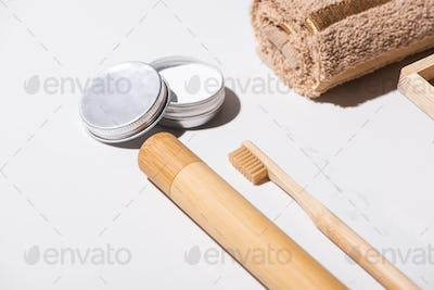 Toothbrush case, toothbrush, towel and jar of wax on white background, zero waste concept