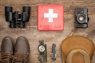 top view of red first aid kit, binoculars, photo camera, boots, hat, compass and jackknife