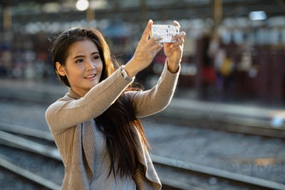 Young beautiful Asian woman at the railway station