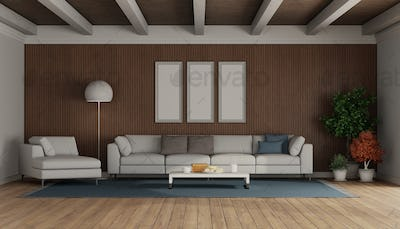 Living room with modern sofa and chaise lounge on wooden paneling
