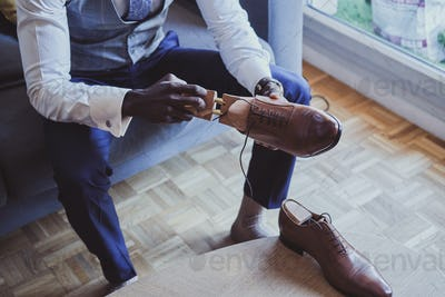 Elegant man is putting on his shoes