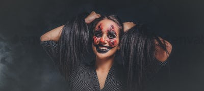 Portrait of evil creepy clown at dark photo studio