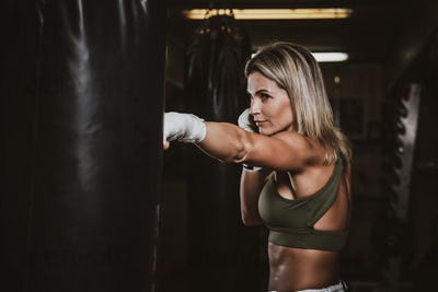 Portrait of female boxer on her training with punching bag