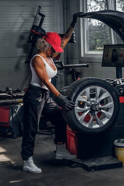 Woman is fixing part of broken car