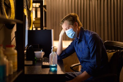 Stressed young businessman with mask looking tired while working from home late at night