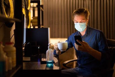 Young businessman with mask holding coffee and using phone at home while working late at night