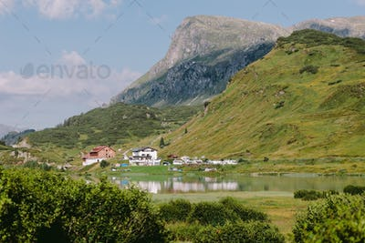 beautiful mountain village with lake and green hills