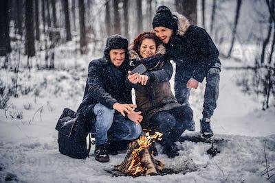 Friends doing selfies near the campfire
