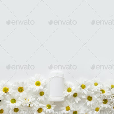 Flat lay composition with deodorant and flowers on white background with copy space