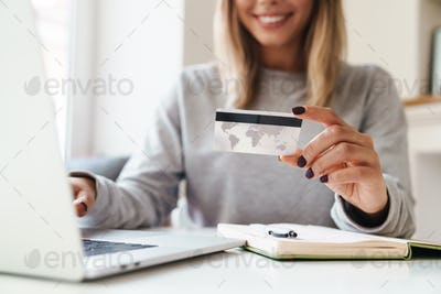 Cropped photo of woman using laptop while holding credit card