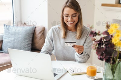 Photo of smiling woman using laptop while holding credit card