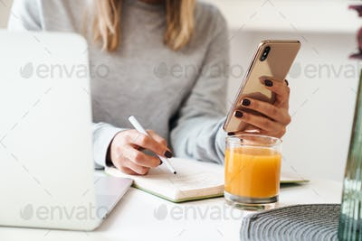 Cropped photo of woman making notes in planner while using cellphone