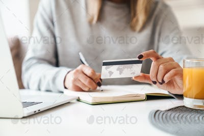 Cropped photo of woman making notes in planner while holding credit card