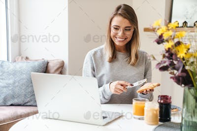 Photo of cheerful woman in eyeglasses eating toasts while using laptop