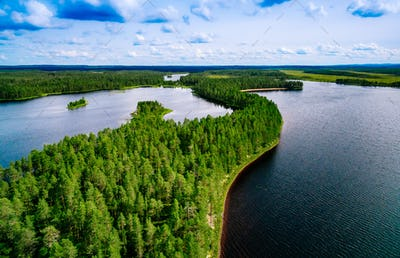 Aerial top view of blue lakes with islands and green forests in Finland.