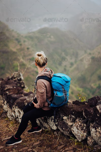Female hiker with blue backpack staying on the stony cobbled trekking trail leading down to the