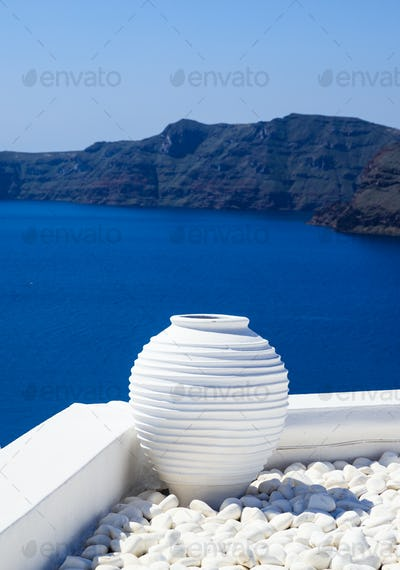 Santorini, Greece. White terrace with ceramic pot and pebbles against blue sea and sky background.