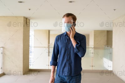 Young man with mask and face shield talking on the phone at modern building