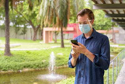 Young man with mask and face shield for protection from corona virus outbreak using phone at the