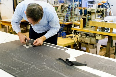 Tailor bending over a workbench cutting fabric