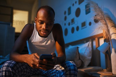Adult African Man Sitting on Bed and Holding Smartphone