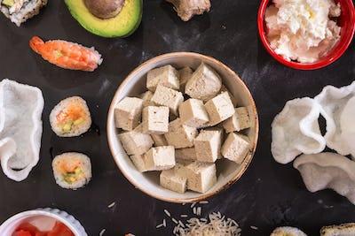 Tofu cheese and sushi on a dark background