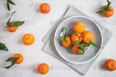 Tangerines on white wooden background. Grey polka dot fabric