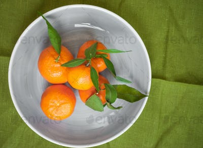 Tangerines on green fabric background