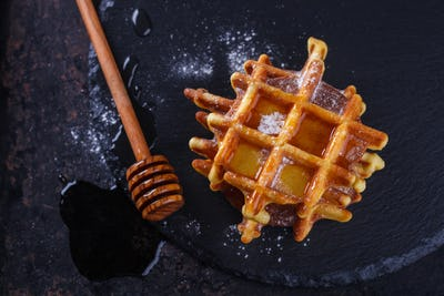 Belgian waffles with honey on a black background.